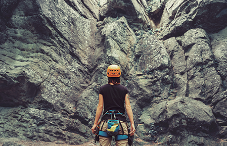 A Woman staring at a rock face she is about to climb. Stay Motivated.