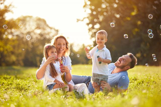Une famille faisant des bulles dans un champ