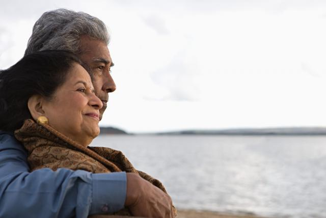 Un couple âgé enlacé au bord d'une plage
