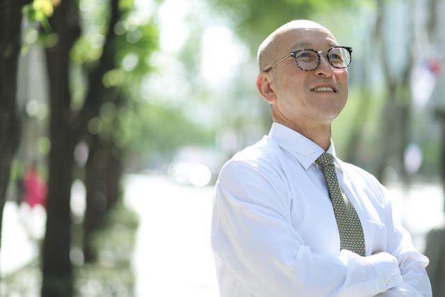 Un homme souriant portant des lunettes avec les bras croisés