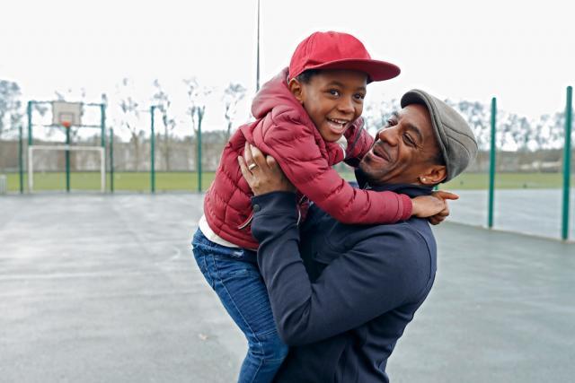 Un homme souriant portant son fils sur un terrain de basketball