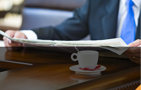 man reading a newspaper with a coffee trying to quit cold turkey