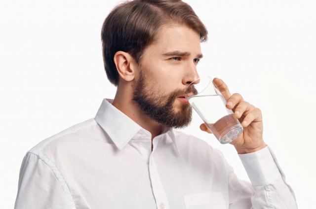 Un homme qui boit un verre d'eau