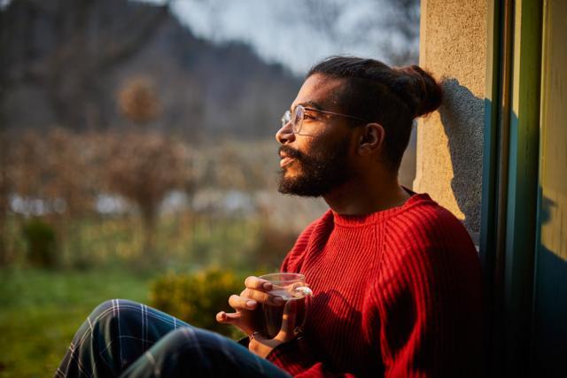 Un homme tenant une boisson et regardant par la fenêtre