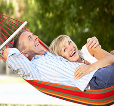 A couple laughing, swinging in a hammock